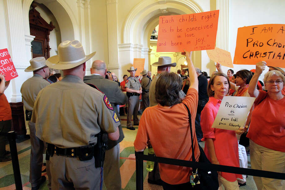 Protestors shread fabric to make headbands as supporters of both sides of the issue fill the Capitol building in Austin as a special committee hears testimony on Senate Bill 2  on July 1, 2013. Photo: Tom Reel, San Antonio Express-News