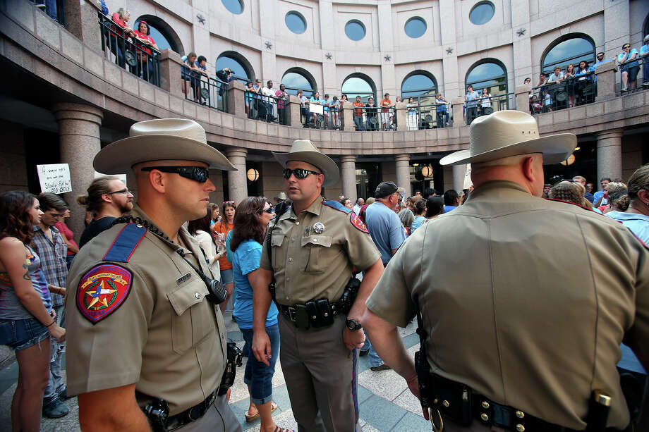 DPS officers wait on the side as supporters of both sides of the issue fill the Capitol building in Austin as a special committee hears testimony on Senate Bill 2  on July 1, 2013. Photo: Tom Reel, San Antonio Express-News