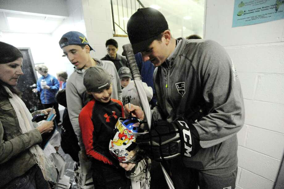 Jonathan Quick signs Cameron Smith's goalie helmet after the NHL's Jonathan Quick Goalie Camp at Stamford Twin Rinks on Tuesday, July 2, 2013. Photo: Jason Rearick / Stamford Advocate