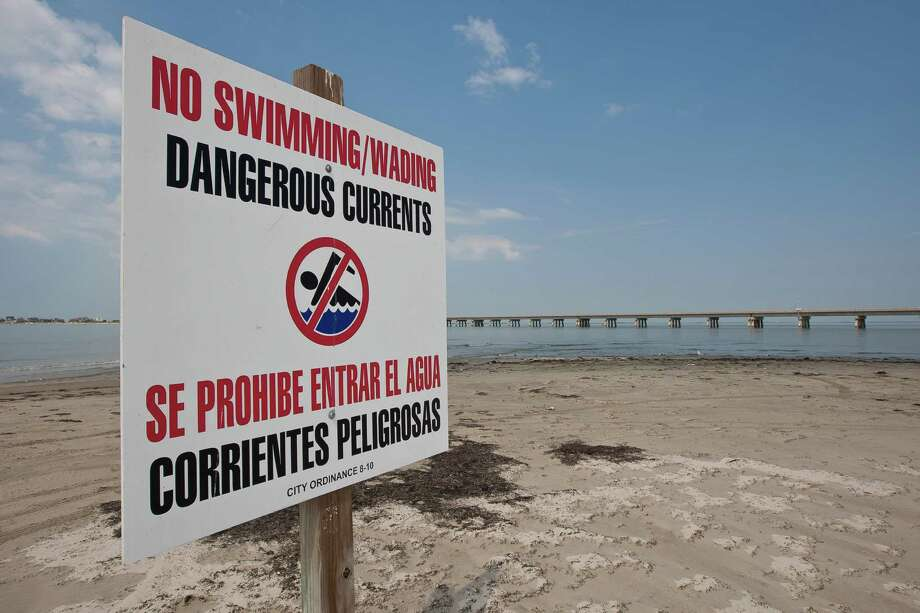 Caution signs are posted along the beach at San Luis Pass, where four swimmers have drowned in the past few weeks.  Galveston will have more beach patrols and police on duty over the July Fourth weekend. Photo: Nick De La Torre, Staff / © 2013  Houston Chronicle