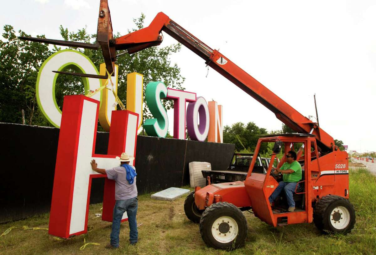 """Jesus Flores, left, and Filipe Torres raise the H on David Adickes' latest artwork, a 30-foot-tall """"We (heart) Houston"""" sign, on Tuesday near Interstate 10 and Patterson."""