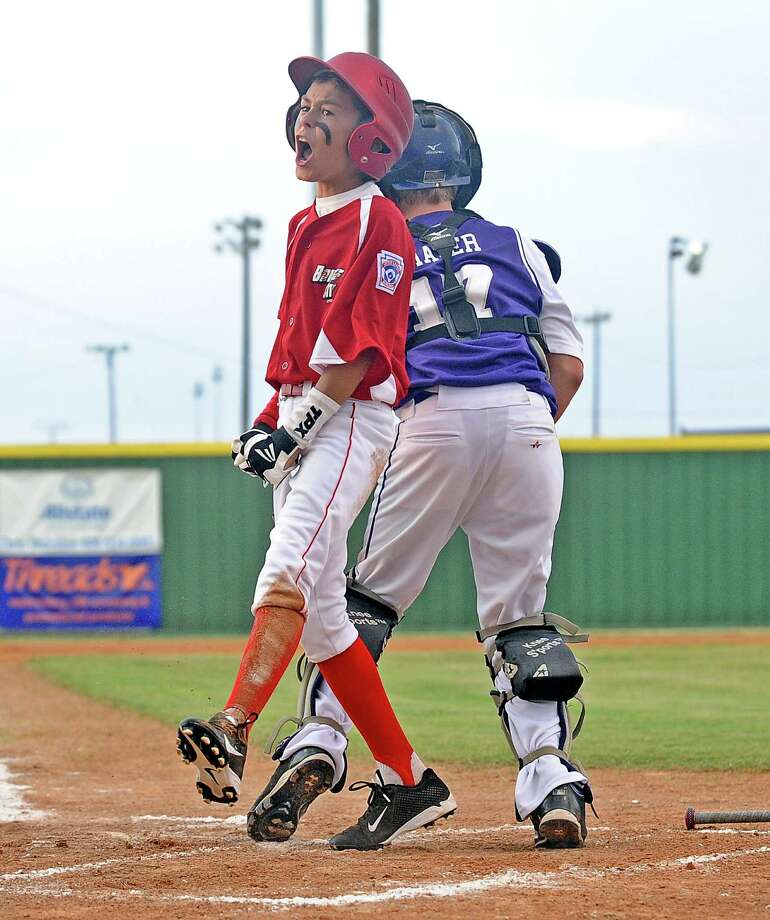Bridge City player Gavin Green, #9, celebrates a close play at home after being called safe during the Bridge City Little League 12-year-old baseball all-stars game against  Port Neches Little League on Tuesday, July 2, 2013. Photo taken: Randy Edwards/The Enterprise Photo: Randy Edwards