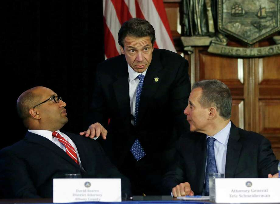 New York Gov. Andrew Cuomo, center, talks with Albany County District Attorney David Soares, left, and New York Attorney General Eric Schneiderman before a news conference at the Capitol on Tuesday, July 2, 2013, in Albany, N.Y. Cuomo has established a powerful investigative body to examine the state Board of Elections and potential wrongdoing by legislators in campaign fundraising. Cuomo announced his attentions two weeks ago after abandoning efforts this year at legislative reforms. That followed federal bribery and embezzlement charges filed against several state lawmakers. (AP Photo/Mike Groll) ORG XMIT: NYMG101 Photo: Mike Groll / AP