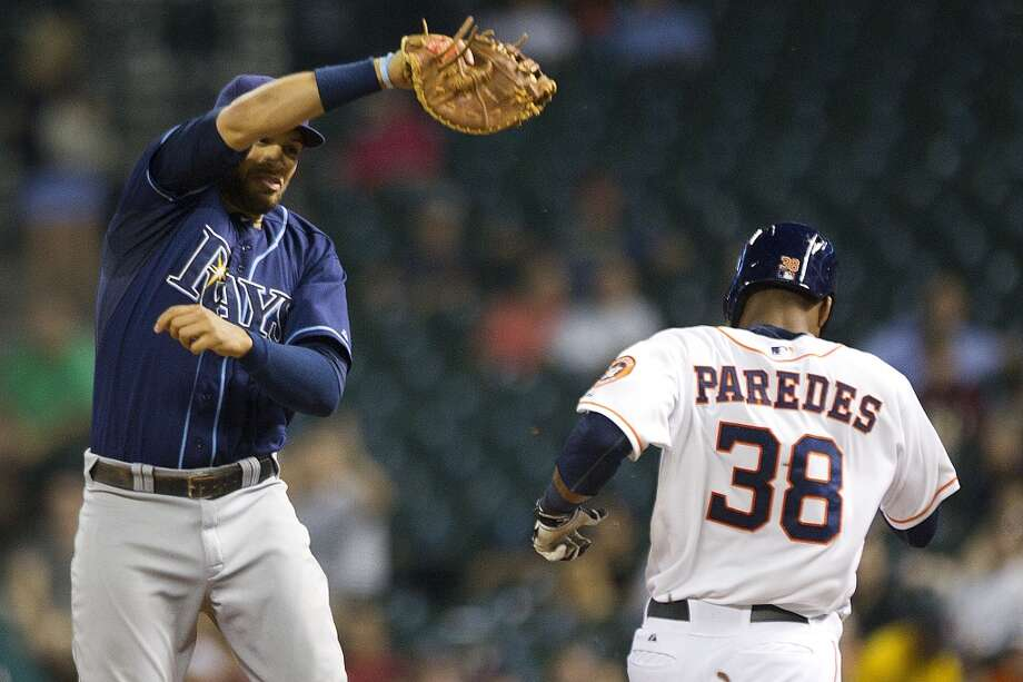 Astros right fielder Jimmy Paredes runs past the tag of Rays first baseman James Loney for an infield hit during the third inning.