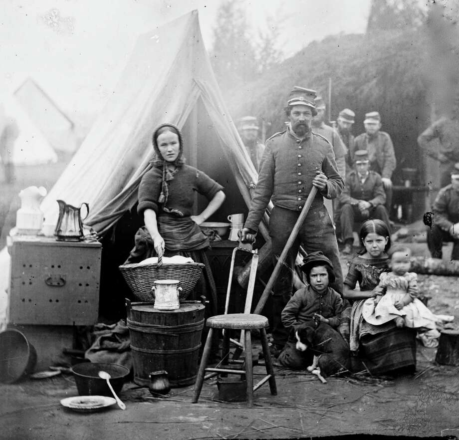 Tent life of the 31st Penn. Inf. (later, 82d Penn. Inf.) at Queen's farm, vicinity of Fort Slocum, Washington, DC, 1861. The husband and wife stand with children and a baby. The wife does the wash and is surrounded by kitchen utensils. Photo: Buyenlarge, Getty Images / Archive Photos