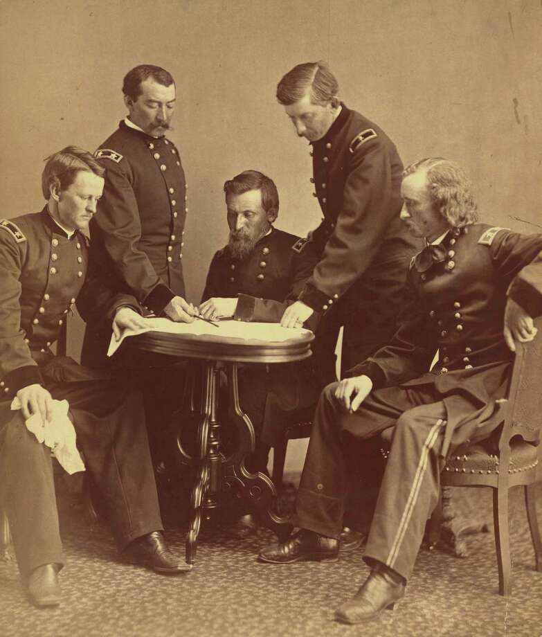 Copy of a photograph showing a group portrait of Union Army generals, from left, Wesley Merritt, Philip Sheridan, George Crook, James William Forsyth, and George Armstrong Custer, gathered around a table examining a document, Washington, DC, 1865. (Photo by Alexander Gardner/Interim Archives/Getty Images) Photo: Interim Archives, Getty Images / Archive Photos