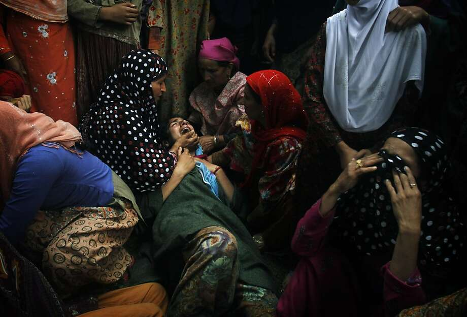 Relatives cry near the body of Shahnawaz Mir, a suspected militant commander of Hizb-ul Mujahedeen, Kashmir's biggest rebel group,  during his funeral at Tral, some 40 kilometers (25 miles) south of Srinagar, India, Tuesday, July 2, 2013. Three Hizb-ul Mujahedeen (HM) militants and a policeman were killed after a fierce gunfight broke out between Indian security forces and militants in this south Kashmir district on Monday. (AP Photo/Mukhtar Khan) Photo: Mukhtar Khan, Associated Press