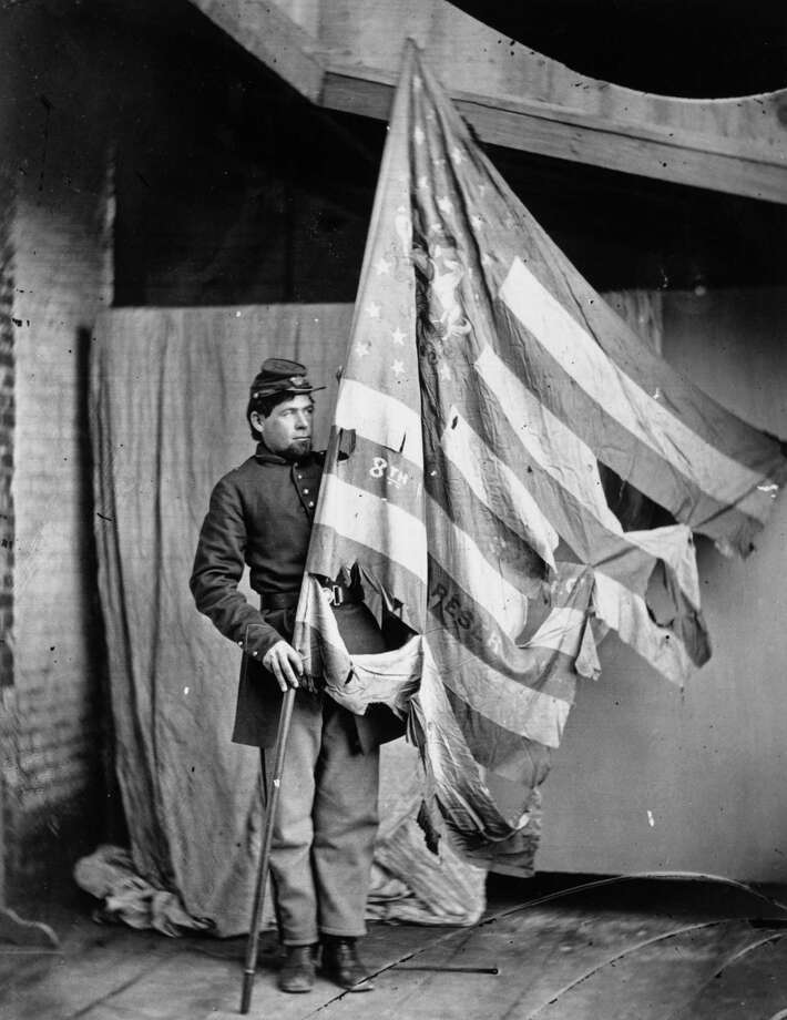 A soldier holding up the torn flag of the 8th Pennsylvania Reserve Colour Guard during the American Civil War. Photo: MPI, Getty Images / Archive Photos