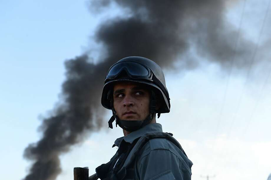 An Afghan policeman stands guard at the site of a suicide attack in Kabul on July 2, 2013. A suicide car bomb in Kabul struck a foreign logistics company supplying NATO forces, killing seven people and wounding three or four others early on July 2, police said. AFP PHOTO/ SHAH MaraiSHAH MARAI/AFP/Getty Images Photo: Shah Marai, AFP/Getty Images