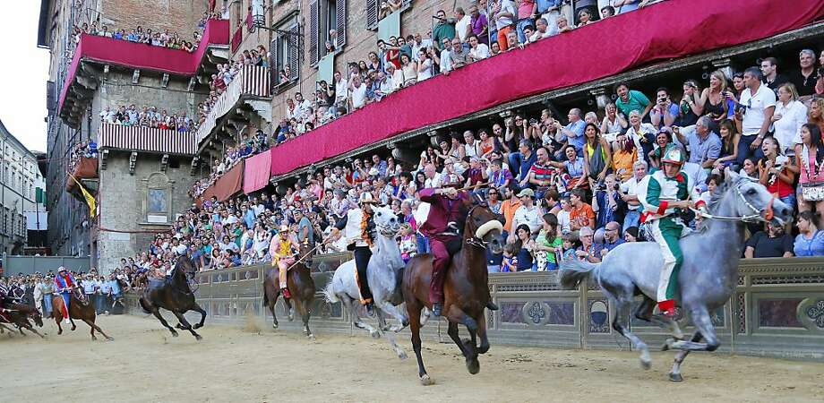 Riders compete during the Palio horse race in Siena on July 2, 2013. The Palio medieval race is held twice a year in Siena with jockeys riding bareback around a makeshift race course set up in the city's central square. AFP PHOTO/FABIO MUZZI FABIO MUZZI/AFP/Getty Images Photo: Fabio Muzzi, AFP/Getty Images