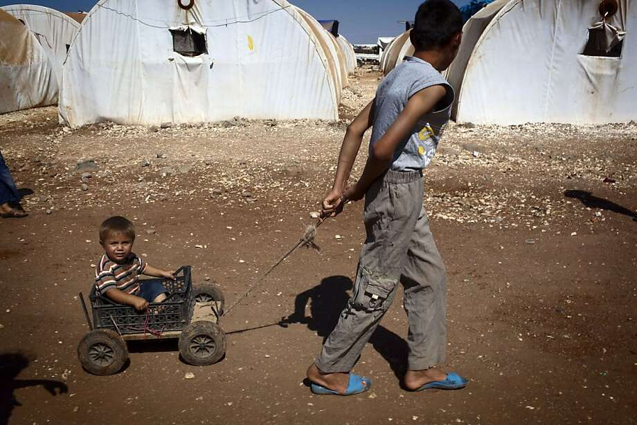 A Syrian boy pulls his younger brother in a cart in the Bab al-Salam refugee camp for displaced Syrians near the border with Turkey on July 2, 2013. US Secretary of State John Kerry said that the United States and Russia were committed to holding a peace conference on Syria but that it would likely take place after August.  AFP PHOTO/JM LOPEZJM LOPEZ/AFP/Getty Images Photo: Jm Lopez, AFP/Getty Images