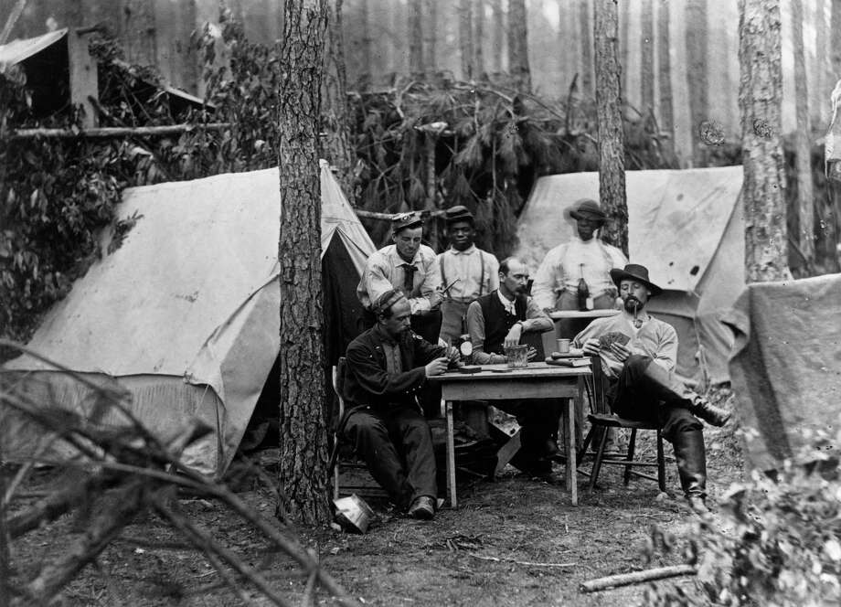 circa 1860s:  Confederate soldiers enjoying a game of poker, a drink and a pipe at their camp site. Photo: MPI, Getty Images / Archive Photos
