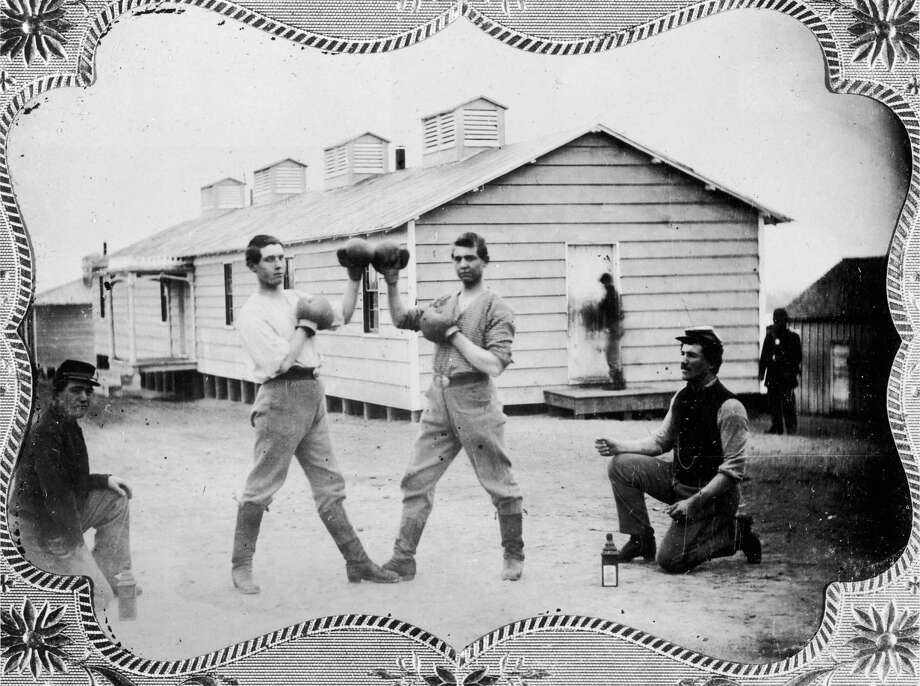 circa 1865: Full-length image of two American soldiers touching their boxing gloves together as they pose before their match in front of a barracks during the Civil War era. Two soldiers crouch on either side of the boxers. Photo: George Eastman House, Getty Images / Archive Photos
