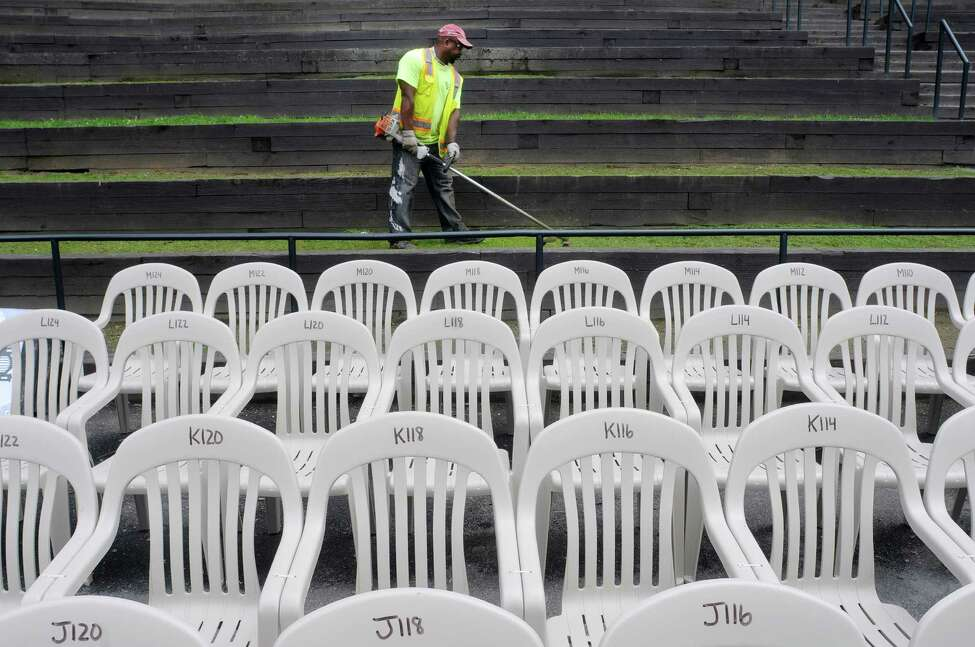 City of Albany Department of Parks employee, Bobby Brown, cuts the grass on the step seating in Washington Park on Tuesday, July 2, 2013 in Albany, NY. The chairs are set up for the Albany Park Playhouse. (Paul Buckowski / Times Union)
