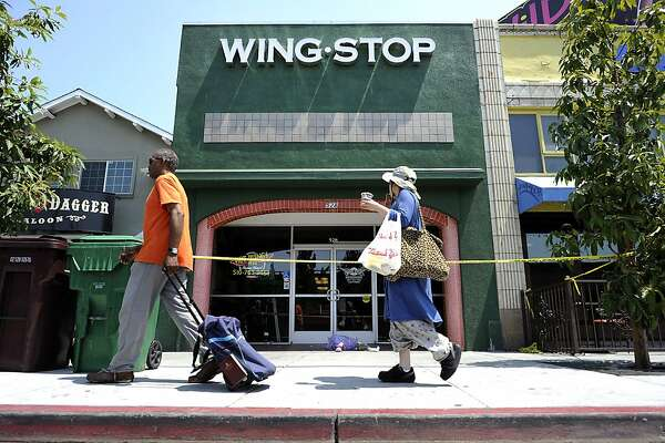 Passers by look at the front of the Wing Stop restaurant on Lake Park Avenue in Oakland, CA Tuesday July 2nd, 2013, which was the scene of an overnight double homicide.
