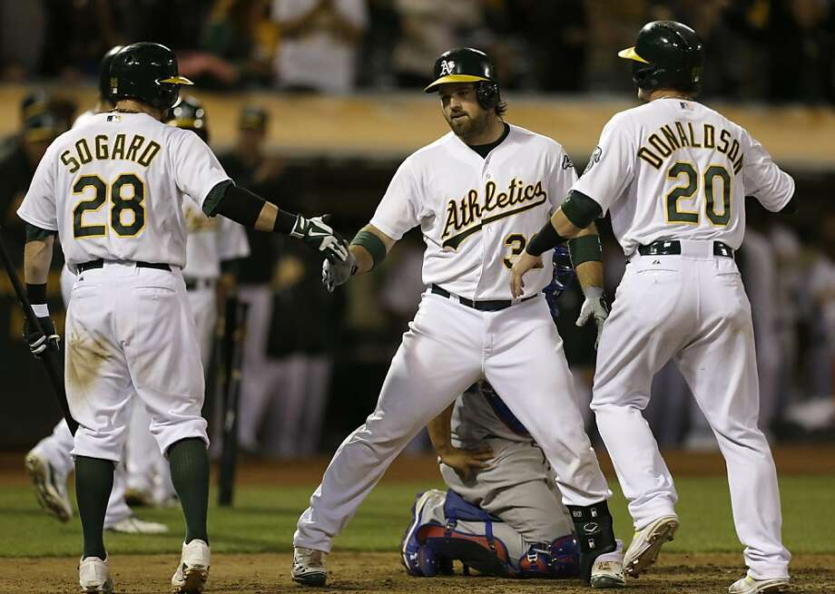 Oakland Athletics' Derek Norris, center, is congratulated by Eric Sogard (28) and Josh Donaldson (20) after Norris hit a three run home run off Chicago Cubs' James Russell in the eighth inning of a baseball game Tuesday, July 2, 2013, in Oakland, Calif. (AP Photo/Ben Margot) Photo: Ben Margot, Associated Press