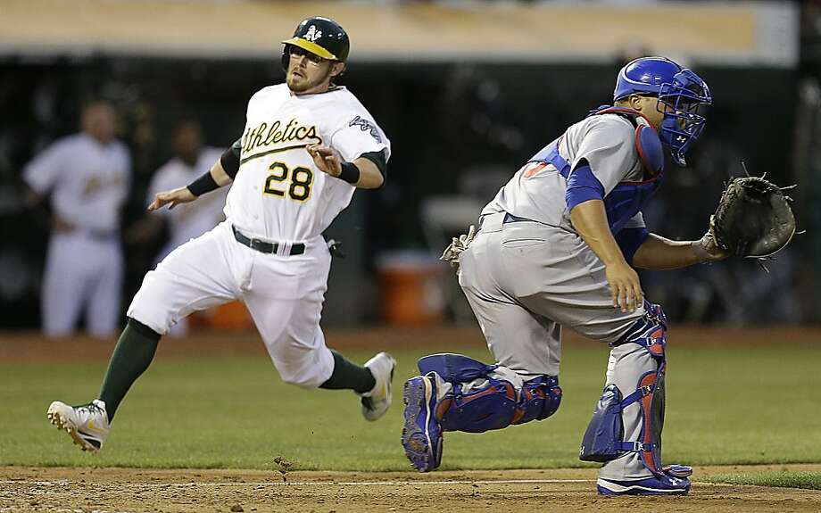 Oakland Athletics' Eric Sogard, left, scores behind Chicago Cubs catcher Welington Castillo in the fourth inning of a baseball game Tuesday, July 2, 2013, in Oakland, Calif. Sogard scored on a single by Coco Crisp.(AP Photo/Ben Margot) Photo: Ben Margot, Associated Press