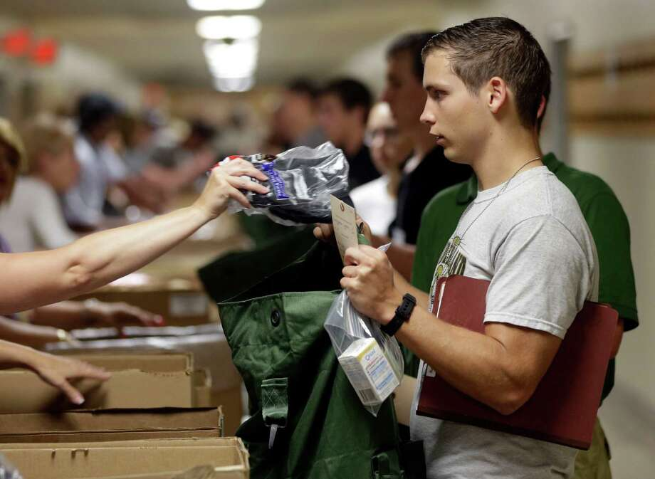 Cadet candidate Sumner Ogrydziak, 17, of Nederland, Texas, collects clothing items during Reception Day at the U.S. Military Academy at West Point on Monday, July 1, 2013, in West Point, N.Y. He and his twin brother Cole and brother Noah, 19, are entering the academy together. Photo: Mike Groll
