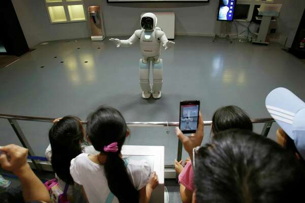 Honda Motor Co.'s interactive robot Asimo talks with visitors at a demonstration event in Tokyo, Wednesday, July 3, 2013. The walking, talking interactive robot ran into glitches in its new job as a museum guide in Tokyo.  During Wednesday's demonstration, the bubble-headed Asimo machine had problems telling the difference between people raising their hands to ask questions and those aiming their smartphones to take photos at the Miraikan science museum.