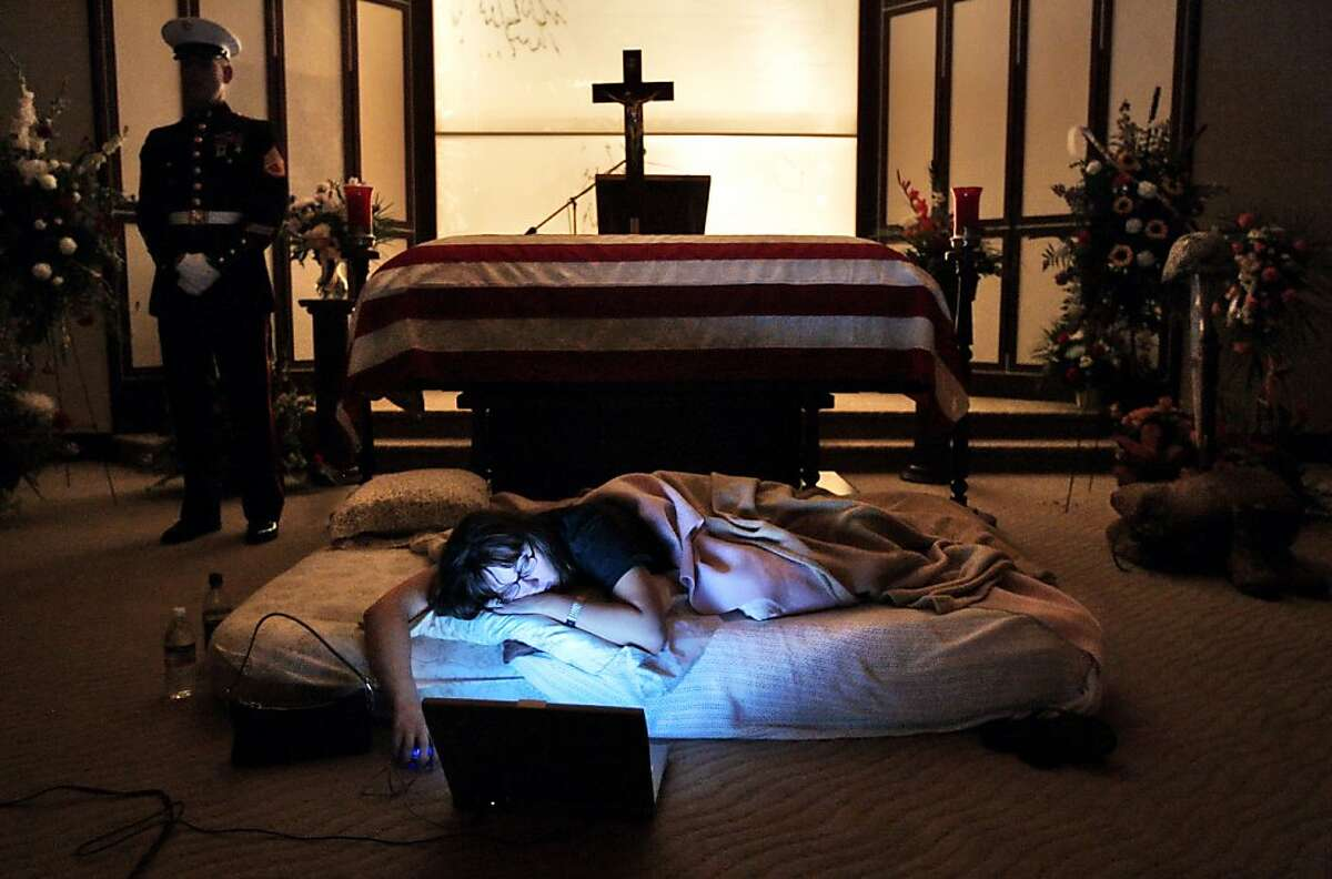 ** This photo is one of the 20 images in Todd Heisler's Final Salute story that was awarded the 2006 Pulitzer Prize for feature photography. The award was announced Monday afternoon April 17, 2006. ** The night before the burial of her husband's body, Katherine Cathey refused to leave the casket, asking to sleep next to his body for the last time. The Marines made a bed for her, tucking in the sheets below the flag. Before she fell asleep, she opened her laptop computer and played songs that reminded her of