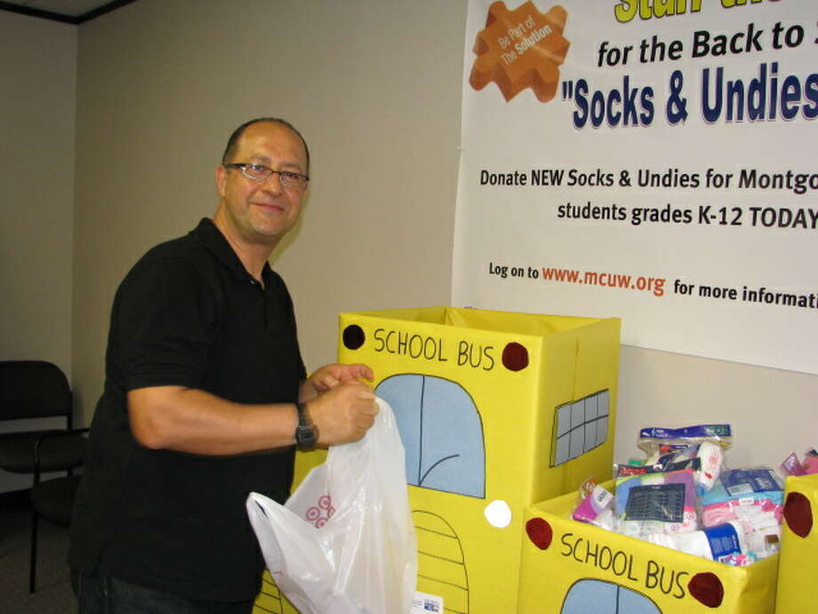 Ruben Correa, editorial director at VIVA! The Magazine, makes a donation in one of the school bus collection boxes for the 9th Annual Socks and Undies Drive on June 21. Photo: Montgomery County United Way