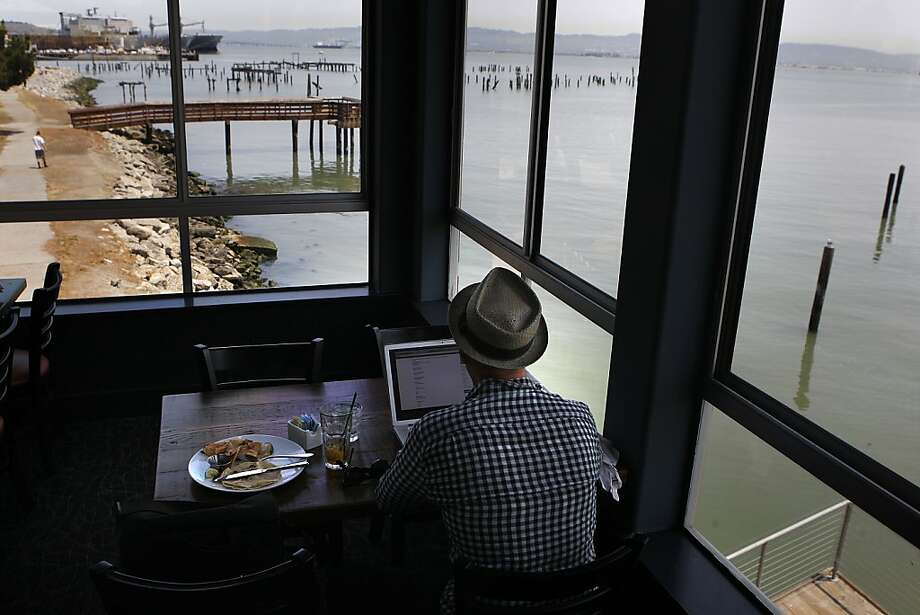 Tommy Becker (left) enjoys lunch and iced tea while surfing the Web at Mission Rock Resort near China Basin and AT&T Park in S.F. Photo: Liz Hafalia, The Chronicle