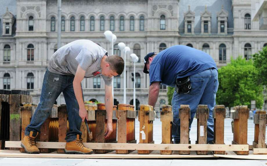 Alonzo Fireworks technicians Scott Braman, left, and Seth Dunn, both from Mechanicville, secure mortar tubes Wednesday morning, July 3, 2013, during  preparation for Thursday night's Price Chopper New York State Fourth of July Celebration at the Empire State Plaza in Albany, N.Y. (Will Waldron/Times Union) Photo: Will Waldron / 00023032A