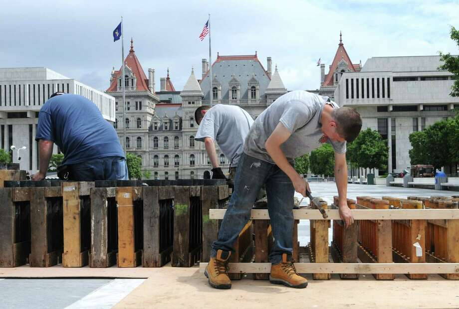 Alonzo Fireworks technicians Seth Dunn, left, Nick Alonzo, center, and Scott Braman, right, mortar tubes Wednesday morning, July 3, 2013, during  preparation for Thursday night's Price Chopper New York State Fourth of July Celebration at the Empire State Plaza in Albany, N.Y. (Will Waldron/Times Union) Photo: Will Waldron / 00023032A