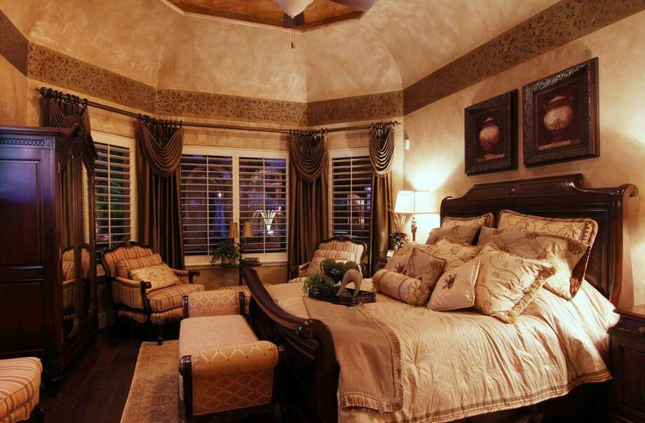 The master bedroom includes custom faux painting andvaulted ceilings. Its windows provide views of the outdoor water fountain.