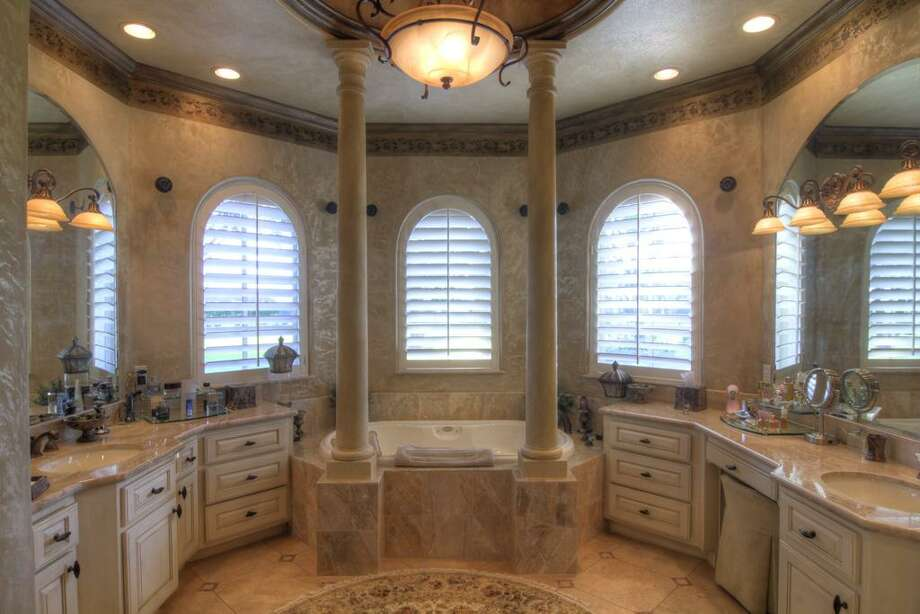 The his-and-hers master bathroom has marble finishes anda whirlpool bath.