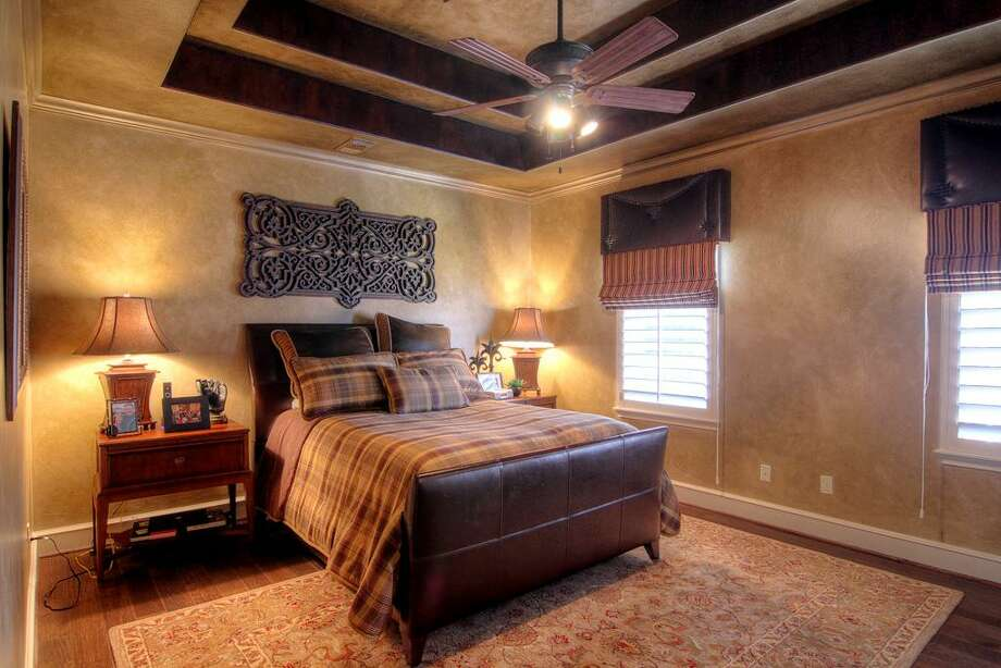 This upstairs bedroom offers a styled ceiling and windows for natural light.