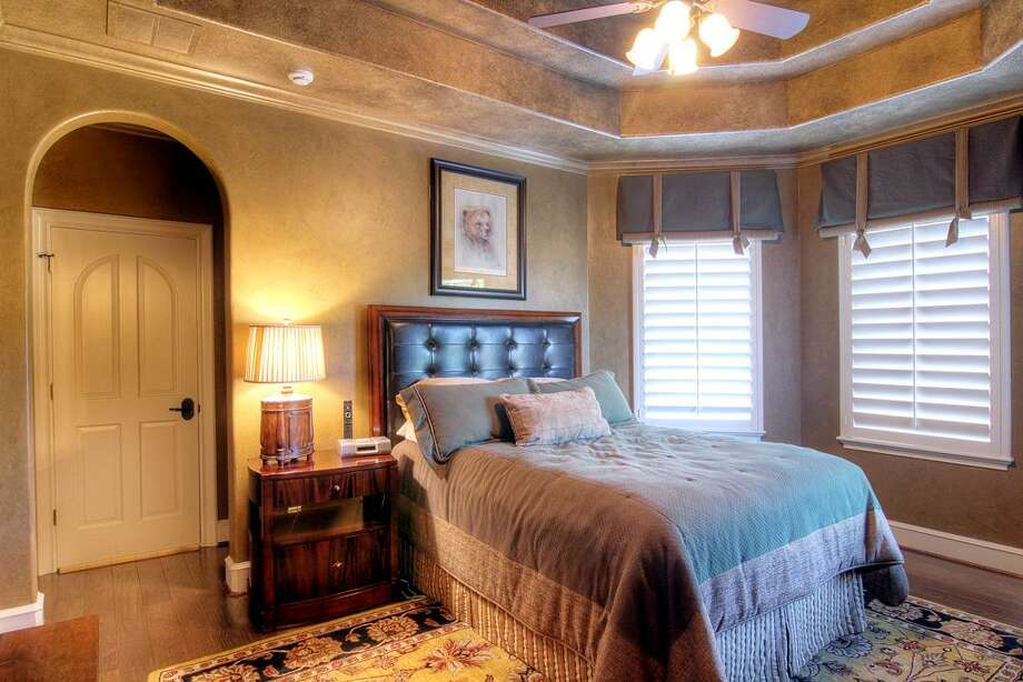 This upstairs bedroom, one of three, has hardwood floorsand a ceiling fan.