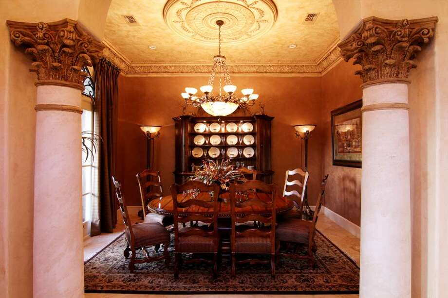The formal dining room features a custom-designedceiling and faux paint.