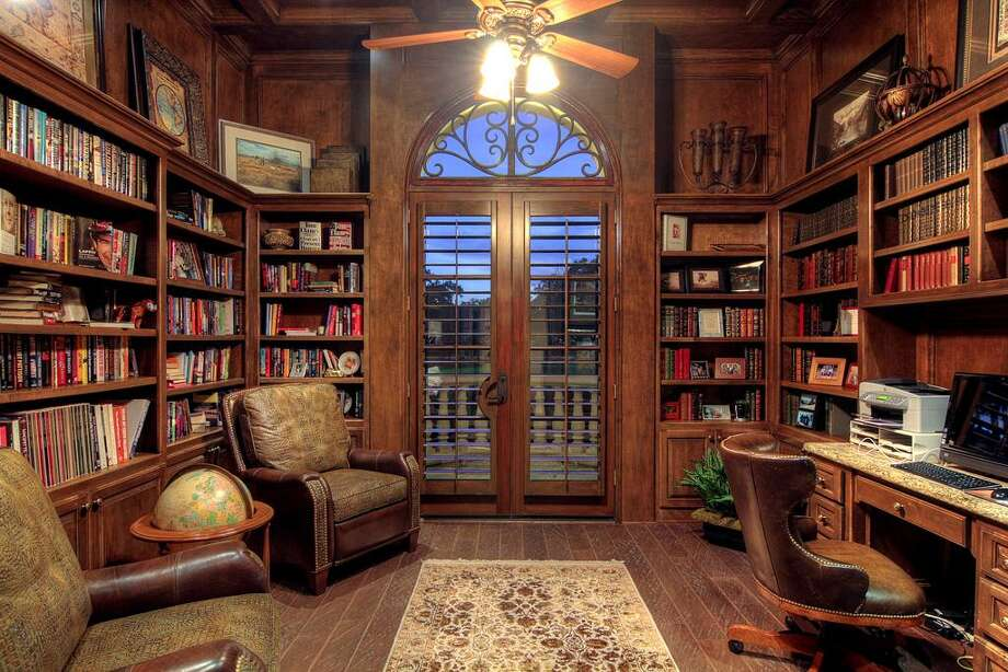 The study features custom built-ins and French doorsleading outside.