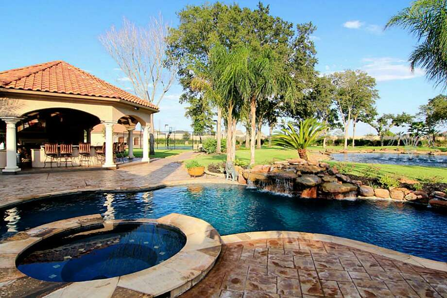 Enjoy relaxing poolside with a rock waterfall, hot tuband nearby outdoor kitchen.
