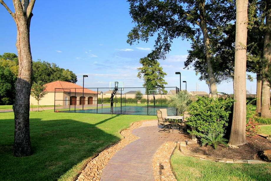 A paved pathway leads to the tennis court and garage.