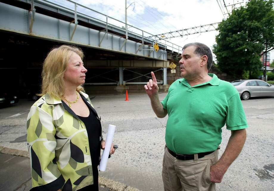 Eva Weller, left, Executive Director of the East Side Partnership, and Simon Cattan, Treasurer, right, stand under the train trestle on East Main Street as they talk about their hopes for a rail station near the location in Stamford, Conn., on Wednesday, July 3, 2013. Photo: Lindsay Perry / Stamford Advocate