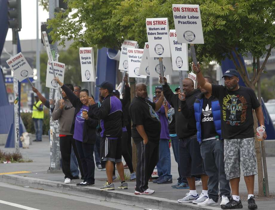 Striking BART workers walk the picket line at the West Oakland station on 7th Street in Oakland, Calif. on Wednesday, July 3, 2013.