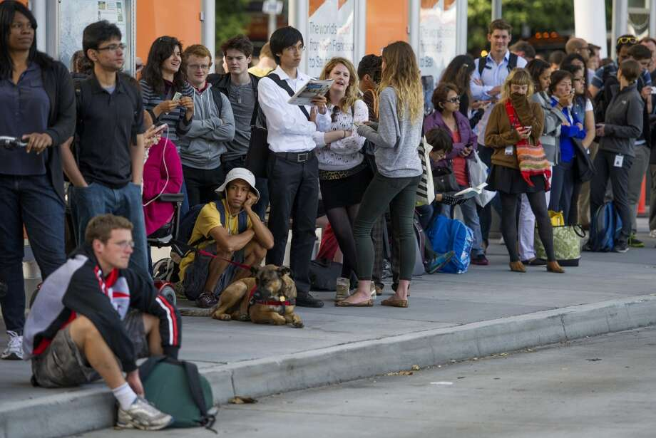 Commuters wait in line at the Temporary Transbay Terminal in San Francisco, California, U.S., on Tuesday, July 2, 2013.