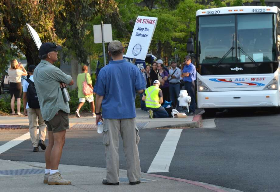 Two BART strikers stand and look towards a long line of commuters working their way down California Boulevard to buses waiting to take them to San Francisco on the second day of the BART strike in Walnut Creek, Calif., on Tuesday, July 2, 2013.