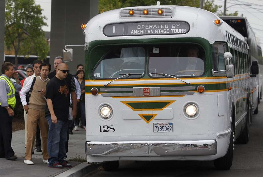Commuters board a vintage 1958 passenger bus, pressed into service from the Pacific Bus Museum,  for a trip to San Francisco, at the West Oakland BART station in Oakland, Calif. on Wednesday, July 3, 2013.