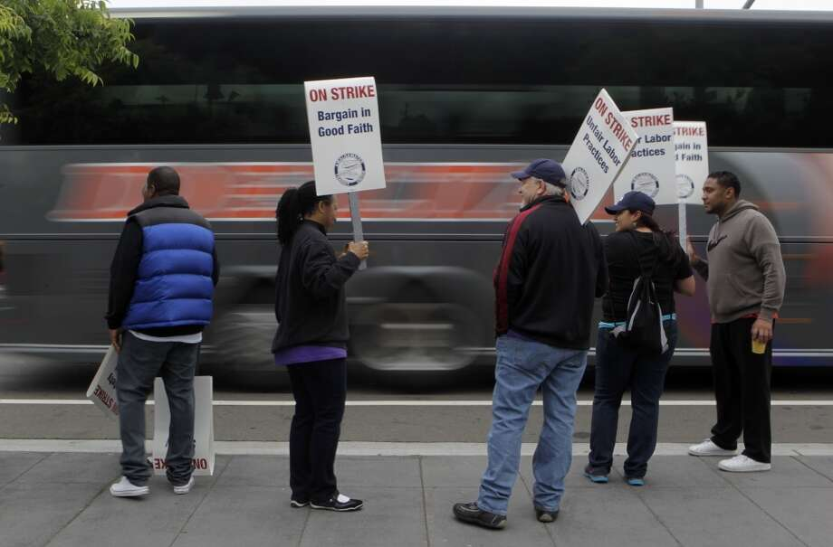 A shuttle bus carrying commuters to San Francisco rolls past striking BART workers at the West Oakland station in Oakland, Calif. on Wednesday, July 3, 2013.