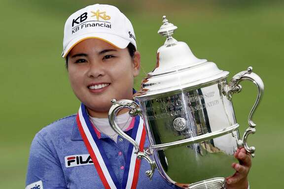 Inbee Park, of South Korea, holds the championship trophy after winning the U.S. Women's Open golf tournament Sunday.