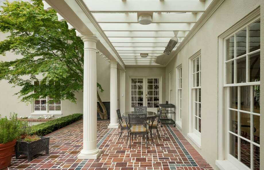 Patio of 260 39th Ave. E., in Denny-Blaine. The 10,690-square-foot mansion, built in 1921, has seven bedrooms, 5.5 bathrooms, a grand entry, a sunroom, a two-story library, five fireplaces, French doors, an elevator, a wine cellar, a recreation room and a pool on more than three-quarters of an acre. It's listed for $6.78 million. Photo: Courtesy Virginia And Whitney Mason, Coldwell Banker Bain