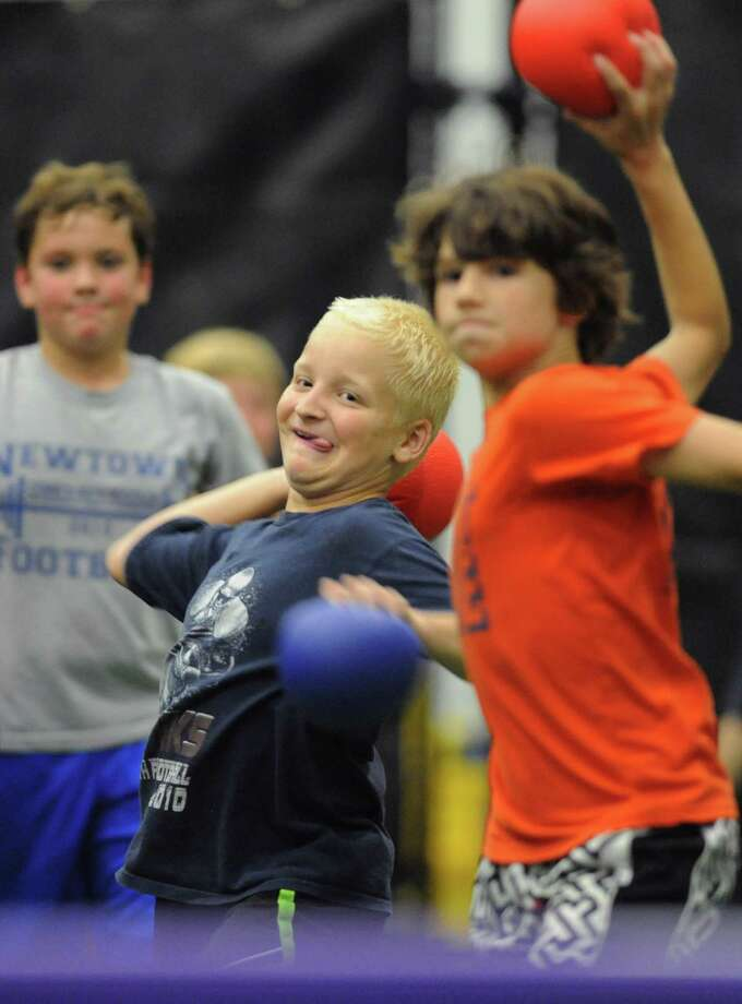 Newtown 10-year-olds Colton Stergue, left, and Will Wallace, right, throw balls at the other team during Average Joe's drop-in dodgeball night at NYA Sports & Fitness Center in Newtown, Conn. on Tuesday, August 2, 2013. Photo: Tyler Sizemore / The News-Times