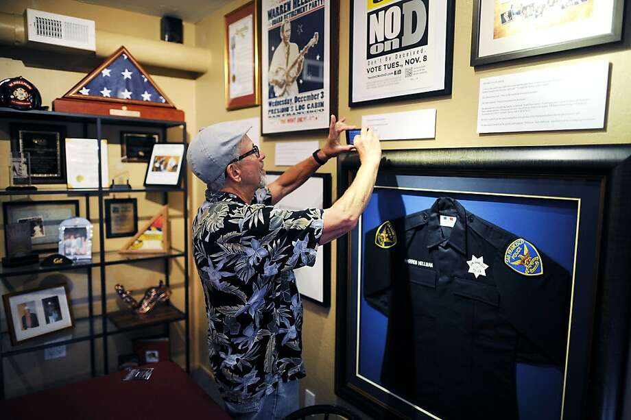 Dan Howard of San Francisco snaps a shot of a wall display at the Warren Hellman Museum. The venue features items from the philanthropist's Presidio Heights home, including furniture and TV monitors for the galleries, plus photo albums and scrapbooks. Photo: Michael Short, Special To The Chronicle