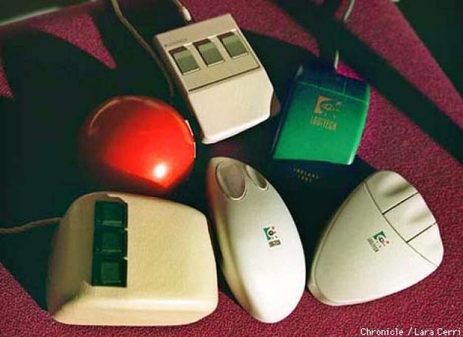 "Mice through thte ages: The evolution of the mouse includes a 1968 model by ""Father of the Mouse"" Doug Engelbart (lower left). From that evolved Logitech devices including (clockwise) a red 1981 model; a simple square in 1985; the green 1989 model; and finally the 1992 and 1996 wireless mice."