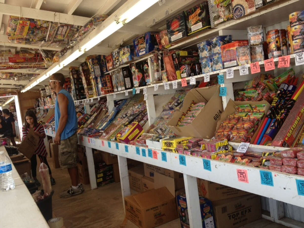 Alamo Fireworks stand worker Jerry Marshall tends to customers before the July 4th holiday.