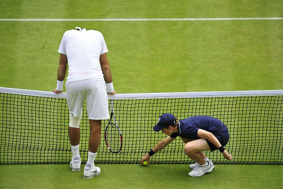 Argentina's Juan Martin Del Potro (L) reacts to netting the ball after a rally against Spain's David Ferrer as the ballboy collects a ball during their men's singles quarter-final match on day nine of the 2013 Wimbledon Championships tennis tournament at the All England Club in Wimbledon, southwest London, on July 3, 2013. AFP PHOTO / GLYN KIRK GLYN KIRK/AFP/Getty Images Photo: Glyn Kirk, AFP/Getty Images