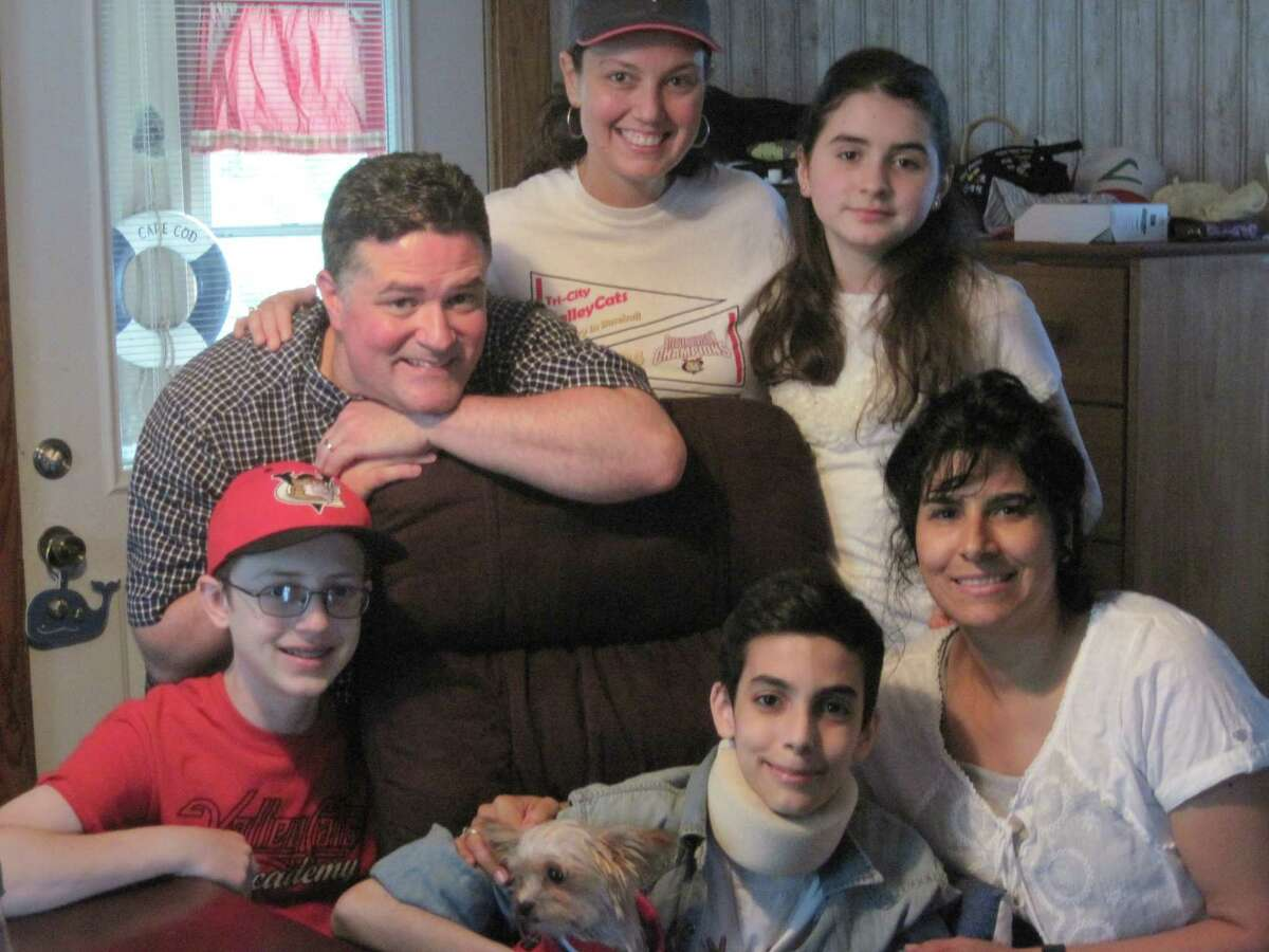 Connor Moran with his dog, Frodo Baggins, center, pose at his home in Wynantskill with family friends (from left) Matthew Ruotolo, Richard Ruotolo and Michelle Ruotolo, sister Kirsten and mother Laura on Wednesday, June 26, 2013. (Jennifer Patterson/Times Union)